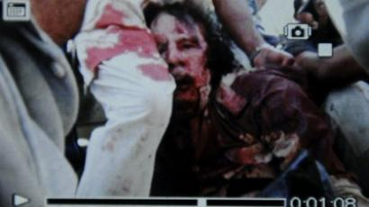 PHOTO: An image captured off a cellular phone camera shows the arrest of Libya's strongman Muammar Gaddafi in Sirte on October 20, 2011 (AFP Photo / Philippe Desmazes)VIDEO: Amateur video purportedly showing dead Gaddafi