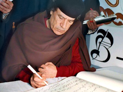 South Africa, Cape Town: Libyan President Muammar Gaddafi signs the guestbook after he toured the prison on Robben Island which was the home of South African President Nelson Mandela for many years, off Cape Town 14 June 1999 (AFP Photo)