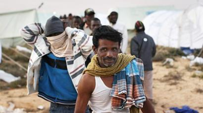 Men who recently crossed into Tunisia  from Libya  walk through a United Nations displacement camp on March 10, 2011 in Ras Jdir, Tunisia