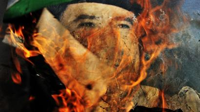 A portrait of Libyan leader Colonel Moamer Kadhafi burns after rebels set fire to it in the town of Bin Jawad (AFP Photo / Aris Messinis)