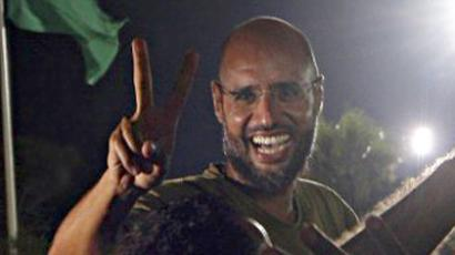 Libya, Tripoli: Saif al-Islam Kadhafi, son of Libyan leader Moamer Kadhafi, flashes the V-sign for victory as he appears in front of supporters and journalists at his father's residential complex in the Libyan capital Tripoli in the early hours of August 23, 2011. (AFP Photo / Imed Lamloum)