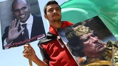 A Palestinian youth holds a poster of Libyan leader Moamer Kadhafi (R) and that of his son Saif al-Islam (AFP Photo / Mahmud Hams)