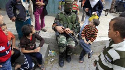 Children look at an Islamic Jihad militant in Beit Lahia in the northern Gaza Strip on November 4, 2011 (AFP Photo/Mohammed Abed). Watch the video: that is how a pharmaceutical disaster looks like.