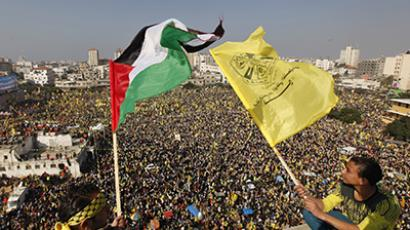 Palestinians wave a Palestinian (L) flag and a Fatah flag during a rally marking the 48th anniversary of the founding of the Fatah movement, in Gaza City January 4, 2013. (Reuters / Mohammed Salem)
