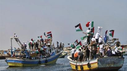 "Mediterranean Sea: Palestinians waving national flags wait aboard fishing boats at the port of Gaza City on May 30, 2010 to greet the so-called ""Freedom Flotilla"". (AFP Photo / Mahmud Hams)"