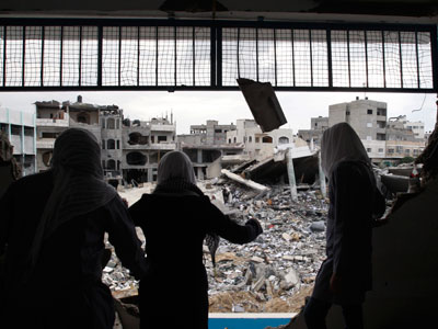 Palestinian school girls look at destroyed buildings from their school, which witnesses said was damaged in an Israeli air strike, in Gaza City November 24, 2012.(Reuters / Ahmed Zakot)