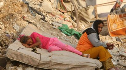 A Palestinian girl sleeps in front of a house, destroyed during the three-week offensive Israel launched in the northern Gaza Strip October 16, 2009 (Reuters / Mohammed Salem)