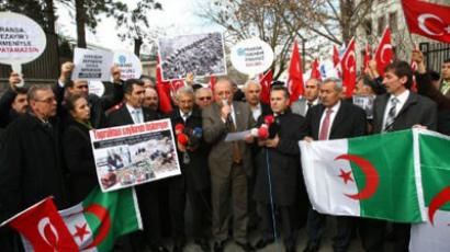 Members of a Turkish pro-government union hold Turkish flags and pictures reportedly showing victims of the French-Algerian war as they shout slogans against France and French President Nicolas Sarkozy outside the French Embassy in Ankara on December 22, 2011 (AFP Photo / ADEM ALTAN)