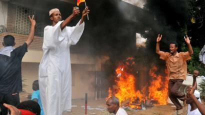 A Sudanese demonstrator burns a German flag as others shout slogans after torching the German embassy in Khartoum during a protest against a low-budget film mocking Islam on September 14, 2012. (AFP Photo/Ashraf Shazly)