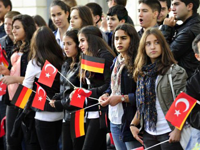 Youths wave German and Turkish flags to greet German President Christian Wulff and Turkey's President Abdullah Gul on September 19, 2011 at Bellevue Palace in Berlin (AFP Photo / JOHN MACDOUGALL)