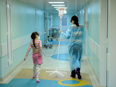 A woman carries a dropper of her daughter, patient of the oncology unit, in the RDKB.(AFP Photo / Natalia Kolesnikova)