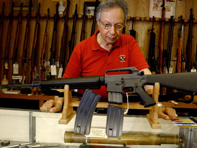 Gun shop manager Stephan Romanoff displays an AR-15 rifle and two magazines (Jeff Swensen/Getty Images/AFP)