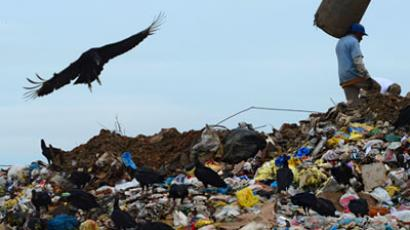 A 'Catador' (scavenger) digs through trash at the Jardim Gramacho landfill, the biggest in South America, in Rio de Janeiro on May 15, 2012 (AFP Photo / Christophe Simon)