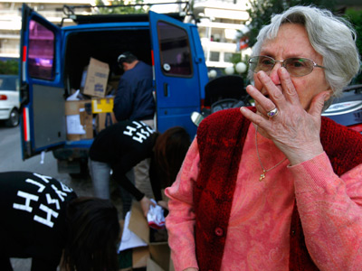 Karousi, former Socialist voter, breaks down in tears as Golden Dawn extreme right party members unload bags of food for her and her husband in Athens (Reuters / Yannis Behrakis)