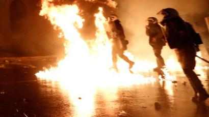 Flames from molotov cocktails flare up near Greek riot police during clashes with protestors at a 48-hour strike by the two major Greek workers unions in central Athens.(Reuters / John Kolesidis)