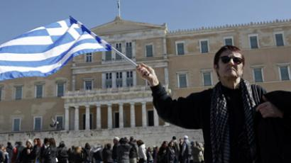A woman raises a Greek flag during an anti-austerity rally in front of the parliament in Athens February 19, 2012. (Reuters / Yiorgos Karahalis)