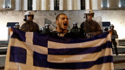 A protester holding a Greek flag shouts slogans during an anti-austerity rally in front of the parliament in Athens February 18, 2012 (Reuters / Yiorgos Karahalis)