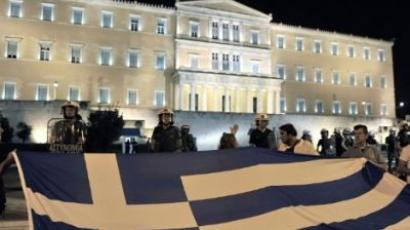 Protesters hold a giant Greek flag during a demonstration in front of the Greek parliament against new austerity measures, as police stand guard, on September 25, 2011. (AFP PHOTO / LOUISA GOULIAMAKI)