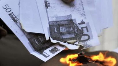 A protestor sets fire to copies of Euro banknotes outside the Bank of Greece headquarters during a global day of action 'against the dictatorship of markets' in Athens on September 17, 2011. (AFP Photo / Louisa Gouliamaki)