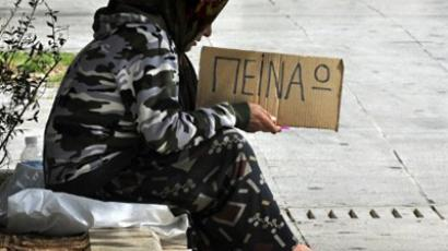 "A woman holds a cardboard reading in Greek ""I' m hungry"" (AFP Photo / Louisa Gouliamaki)"