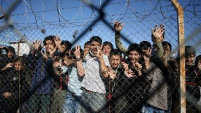 Immigrant minors peer out through the fence of an immigrant detention center in the village of Filakio, on the Greek-Turkish border, upon the arrival there of the Frontex Rapid Border Intervention Teams (RABITs) and EU officials (AFP Photo /Sakis Mitrolidis)