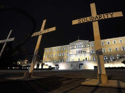 Crosses reading 'Solidarity', 'Dignity ' and 'Freedom' are placed in front of the Greek parliament following the suicide of a retired pharmacist who shot himself.  (AFP Photo/Louisa Gouliamaki)
