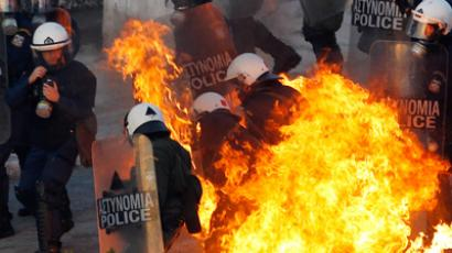 A petrol bomb explodes near riot police during a huge anti-austerity demonstration in Athens' Syntagma (Constitution) square February 12, 2012 (REUTERS / Yannis Behrakis)