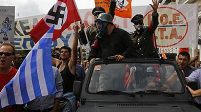 Demonstrators, dressed as Nazis, wave a Greek and a swastika flag as they ride in an open-top car in Syntagma Square in Athens as they protest against the visit of Germany's Chancellor Angela Merkel, October 9, 2012. (Reuters / Yannis Behrakis)