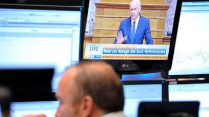 A stockbroker look at his screens, while a television monitor shows Greek Premier Giorgos Papandreou delivering a speech, at the Frankfurt stock exchange in Frankfurt, Germany, November 3, 2011 (AFP Photo / Arne Dedert / Germany Out)