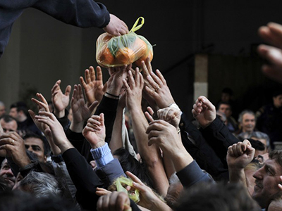 People reach out for a bag of oranges during a free distribution of fruit and vegetables by Greek farmers outside the Agriculture Ministry in Athens, on February 6, 2013. (AFP Photo / Louisa Gouliamaki)