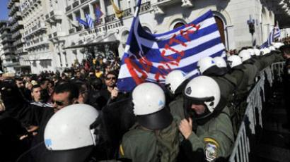 Anti-austerity protesters hold a Greek flag reading 'not for sale' during a student parade in Athens, attended by the Greek minister of education (AFP Photo / LOUISA GOULIAMAKI)