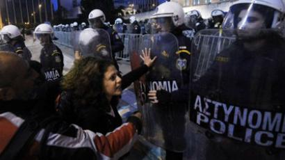 A woman pushes a riot policeman's shield during a protest in front of the Greek parliament near Athen's Syntagma square on April 5, 2012, in reaction to the suicide of an elderly debt-ridden Greek man (AFP Photo / Louisa Gouliamaki)