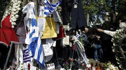 Tributes at the site where a 77-year-old shot himself in the head three days before, at Syntagma Square in Athens, on April 7, 2012. (AFP Photo / Angelos Tzortzinis)