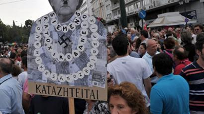 A protester holds a plackard of  German Chancellor Angela Merkel featuring a Hitler moustache near the Greek parliament in Athens during a demonstration against the vist of the German Chancellor Angela Merkel on October 9, 2012. (AFP Photo / Louisa Gouliamaki)