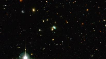 A handout photo released on December 3, 2012 by the European Southern Observatory (ESO) shows thousands of galaxies in the distant Universe viewed from the Canada-France-Hawaii Telescope. But the one close to the center looks very odd — it is bright green.  (AFP Photo/EUROPEAN SOUTHERN OBSERVATORY/M. SCHIRMER)