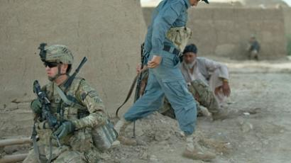 A soldier from 1st Platoon, Delta Coy, 1-64 AR of the US army - operating under NATO sponsored International Security Assistance Force (ISAF) secures a position along with a member of the Afghan National Police during a joint patrol at a settlement near Kandahar Air Field.(AFP Photo / Tony Karumba)