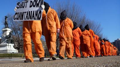 "Members of the group ""Witness Against Torture"" dressed in orange prison jump suits protest against the detention camp at Guantanamo Bay, along Pennsylvania Avenue in Washington D.C. January 10, 2012 (Reuters / Larry Downing)"