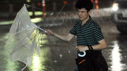 A man walks against strong winds in Tokyo on June 19, 2012 (AFP Photo / Yoshikazu Tsuno)