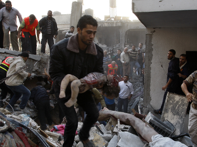 Palestinians carry the dead body of a child from under the rubble of a house after an Israeli air strike in Gaza City November 18, 2012. (Reuters / Ahmed Zakot)