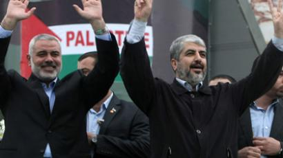 Hamas leader in exile Khaled Meshaal (R) and Hamas prime minister Ismail Haniya (L) gesture to the supporters during a rally to mark the 25th anniversary of the founding of the Islamist movement, in Gaza on December 8, 2012 (AFP Photo / Mahmud Hams)