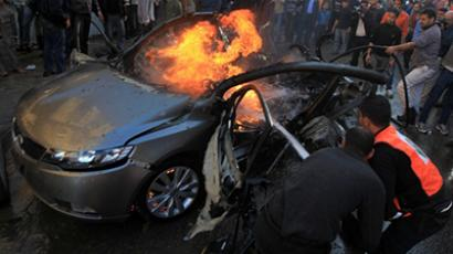 Palestinians extinguish fire from the car of Ahmaed Jaabari,  head of the military wing of the Hamas movement, the Ezzedin Qassam Brigades, after it was hit by an Israeli air strike in Gaza City on November 14, 2012. (AFP Photo / Mahmud Hams)