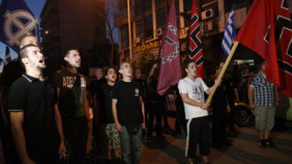 Members of the Greek extreme-right ultra nationalist party Golden Dawn (Chryssi Avghi), sing the National anthem out of the Golden Dawn's office in Thessaloniki on June 17, 2012. (AFP Photo/Sakis Mitrolidis)