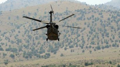 A US Blackhawk army helicopter flies over the mountainous area of Gorbuz district, on the border with Pakistan east of Afghanistan, June 28, 2011. (AFP Photo / Ted Aljibe)