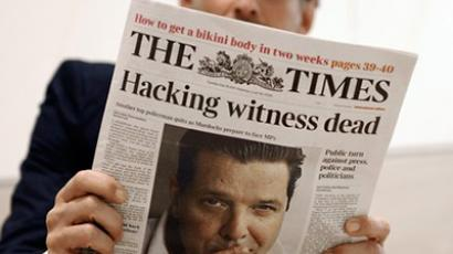 A person reading the British daily newspaper, The Times, the front page of which is on the spiralling phone-hacking scandal (AFP Photo / Getty Images)