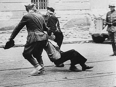 Nazi soldier watching Ukrainians as they drag a Jew down a street in Lvov, 1941