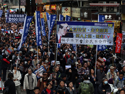 Protesters holding a banner with a picture of Hong Kong chief executive Leung Chun-ying as 'Pinocchio' take part in a pro-democracy rally on New Year's day in Hong Kong on January 1, 2013 (AFP Photo / Aaron Tam)