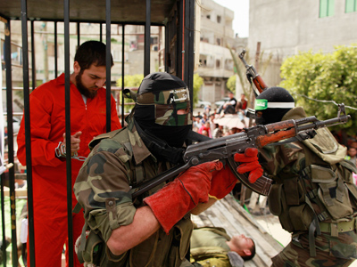Hamas militants stage a mock prison break during a rally, calling for the release of Palestinian prisoners from Israeli jails, in Jabalya, in the northern Gaza Strip, April 13, 2012 (Reuters/Mohammed Salem)