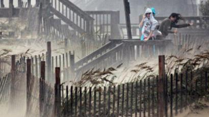 United States, Kill Devil Hills:  People shield themselves from blowing sand and rain as they look over the beach during Hurricane Irene August 27, 2011 in Kill Devil Hills, North Carolina. (AFP Photo / Scott Olson)