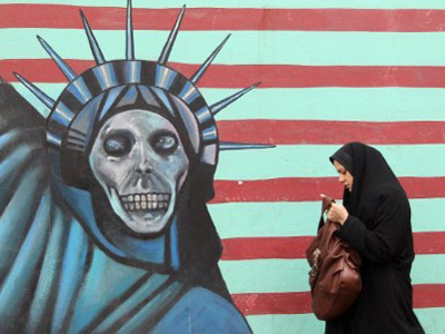 An Iranian woman walks past an anti-US mural painted on the wall of the former US embassy in Tehran on November 19, 201 (AFP Photo / Atta Kenare)