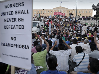 Thousands of immigrants to Greece, mainly from Pakistan gather at Athens central Syntagma square in front of the Greek Parliament on August 24, 2012, during their protest rally against the recent violent attacks on immigrants by ultra nationalist groups and the police operations in order to arrest undocumented immigrants. (AFP Photo/Louisa Gouliamaki)